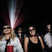 Kinozuschauerinnen mit 3D Brillen lächelnd im Kino